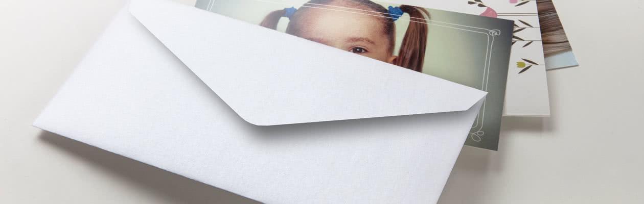 Send Fotokortet ditt med 6 sider i skimrende hvite konvolutter for det lille ekstra.
