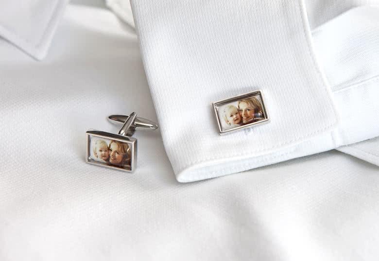 Rechthoekige, zilverkleurige manchetknopen. Foto beschermd door cabochon van epoxyhars